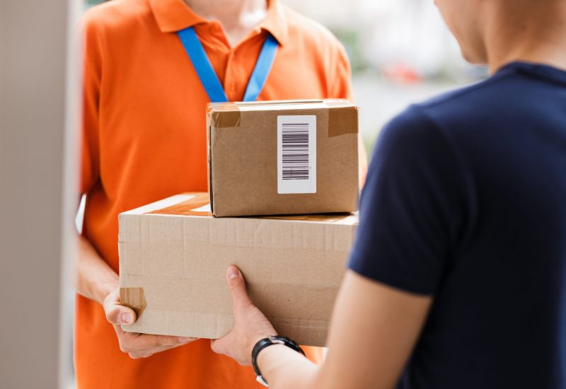 A person wearing an orange T-shirt and a name tag is delivering parcels to a client. Friendly worker, high quality delivery service.